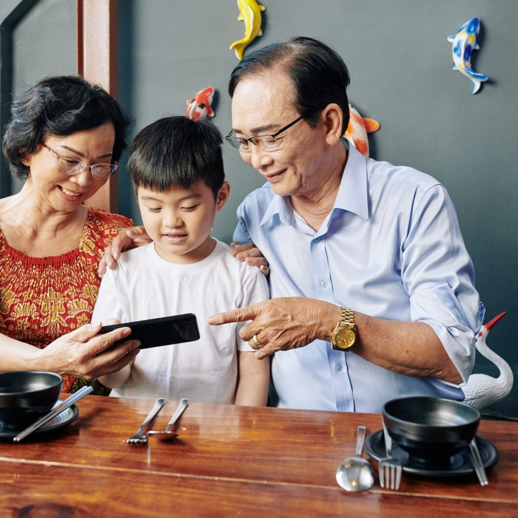 Senior people showing mobile app to grandson